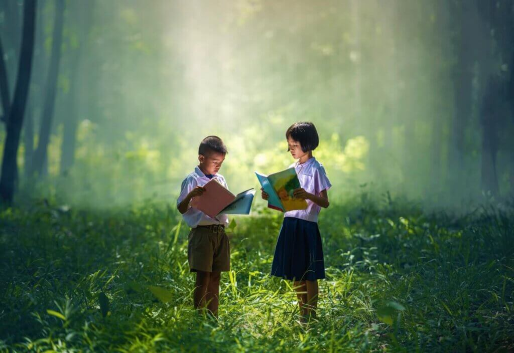 Two kids reading in forest